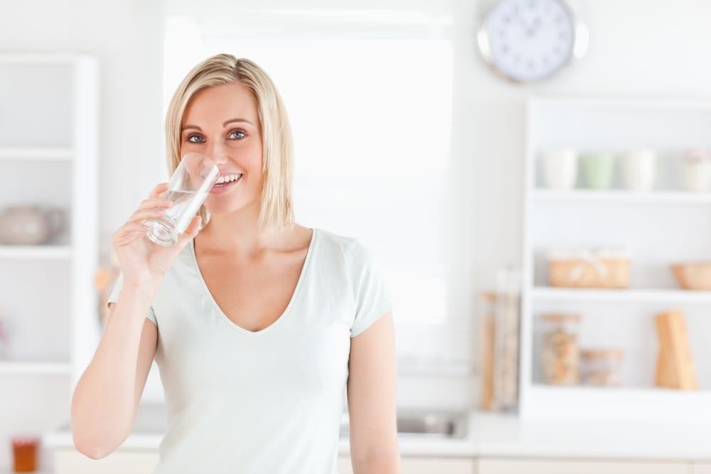 Uśmiechnięta kobieta w białej bluzce pije szklankę wody