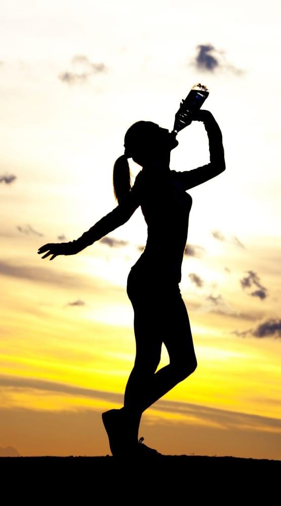 Kobieta pije wodę mineralną na tle zachodzącego słońca