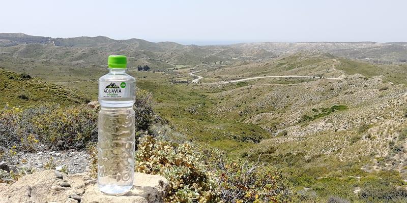 Butelka wody AquaVia na tle wzgórz
