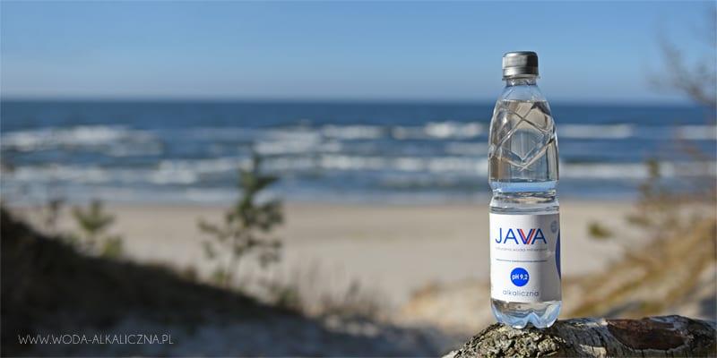 Butelka wody Java na tle morza